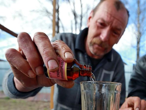 алкоголик наливает настойку боярышника