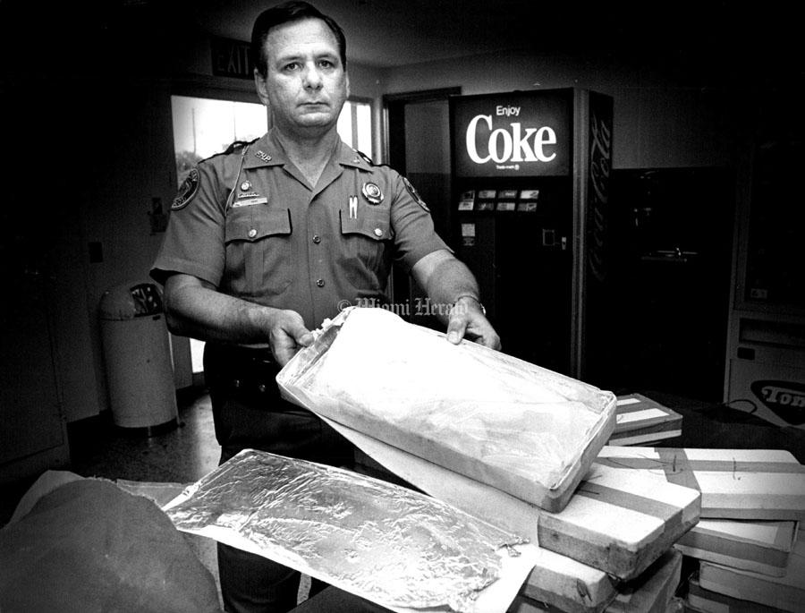 полицейский показывает конфискованную партию кокаина