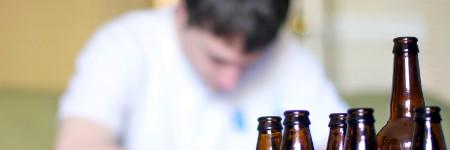 молодой мужчина и бутылки алкоголя