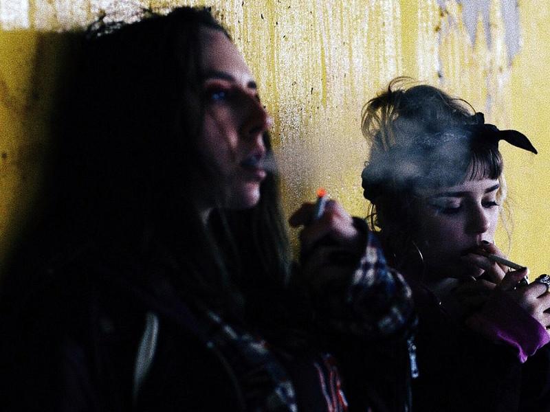 девушки курят у желтой стены